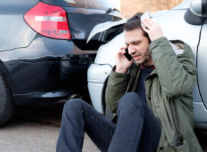 man on the phone calling for help after a car accident